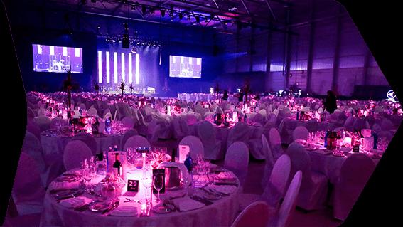 Saalbeleuchtung BDU Nuernberg 2019. Tischdeko in Magenta beleuchtet, Buehne mit LED Leinwaenden und LED Leuten bestueckt.